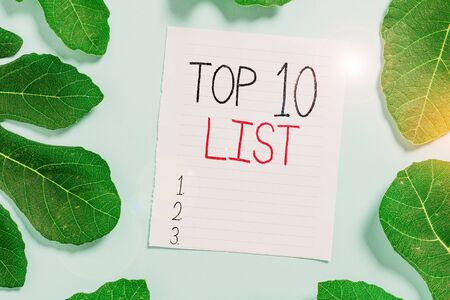 Conceptual hand writing showing Top 10 List. Concept meaning the ten most important or successful items in a particular list Leaves surrounding notepaper above empty soft pastel table Stok Fotoğraf
