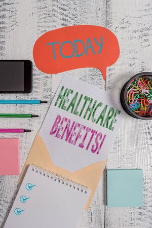 Text sign showing Healthcare Benefits. Business photo showcasing monthly fair market valueprovided to Employee dependents Envelop speech bubble smartphone sheet pens spiral notepads clips wooden
