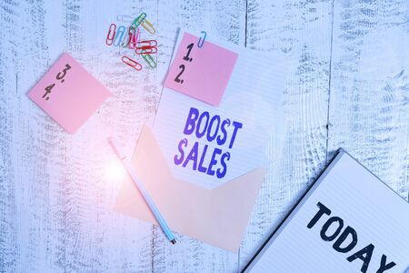 Word writing text Boost Sales. Business photo showcasing move sales profit from a lower to a higher place or position Envelope sheet paper sticky notes ballpoint notepad clips wooden background