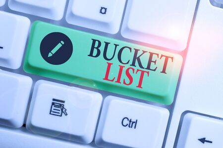 Handwriting text writing Bucket List. Conceptual photo a list of the things that a demonstrating would like to do or achieve White pc keyboard with empty note paper above white background key copy space Standard-Bild