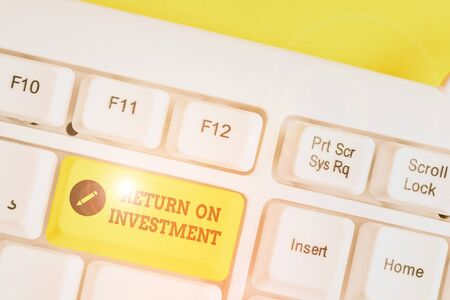Conceptual hand writing showing Return On Investment. Concept meaning Ratio between the Net Profit and Cost invested White pc keyboard with note paper above the white background Reklamní fotografie