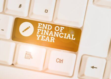 Text sign showing End Of Financial Year. Business photo showcasing Revise and edit accounting sheets from previous year White pc keyboard with empty note paper above white background key copy space