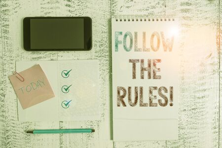 Writing note showing Follow The Rules. Business concept for go with regulations governing conduct or procedure Square spiral notebook marker smartphone sticky note on wood background Standard-Bild - 133486146