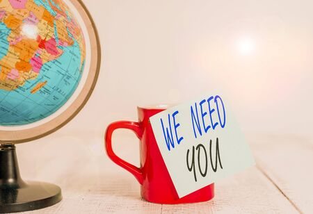 Conceptual hand writing showing We Need You. Concept meaning to fulfill the needs of the assignment duty or obligation Globe map coffee cup sticky note lying vintage wooden table Archivio Fotografico - 133486247