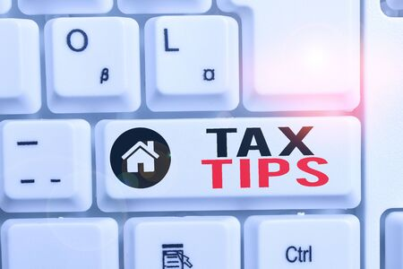 Word writing text Tax Tips. Business photo showcasing compulsory contribution to state revenue levied by government White pc keyboard with empty note paper above white background key copy space