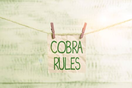 Conceptual hand writing showing Cobra Rules. Concept meaning continuing group health insurance coverage after a job loss Clothespin rectangle shaped paper reminder white wood desk