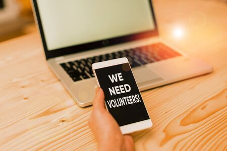 Conceptual hand writing showing We Need Volunteers. Concept meaning someone who does work without being paid for it woman with laptop smartphone and office supplies technology