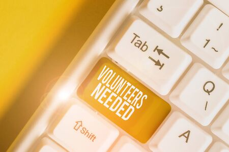Handwriting text writing Volunteers Needed. Conceptual photo need work or help for organization without being paid White pc keyboard with empty note paper above white background key copy space