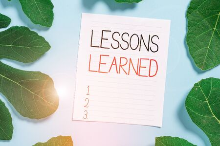 Conceptual hand writing showing Lessons Learned. Concept meaning the knowledge or understanding gained by experience Leaves surrounding notepaper above empty soft pastel table