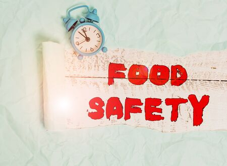 Conceptual hand writing showing Food Safety. Concept meaning conditions and practices that preserve the quality of food Alarm clock and torn cardboard on a wooden classic table backdrop