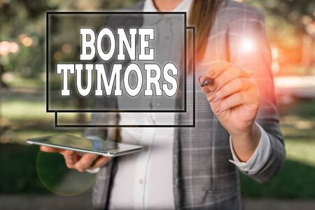 Handwriting text Bone Tumors. Conceptual photo can be either benign or malignant growths found in the bone Outdoor background with business woman holding lap top and pen 스톡 콘텐츠