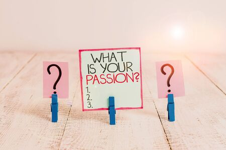 Conceptual hand writing showing What Is Your Passion Question. Concept meaning asking about his strong and barely controllable emotion Crumbling sheet with paper clips placed on the wooden table