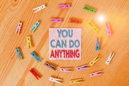 Conceptual hand writing showing You Can Do Anything. Concept meaning Motivation for doing something Believe in yourself Colored crumpled papers wooden floor background clothespin