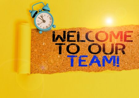 Handwriting text writing Welcome To Our Team. Conceptual photo introducing another demonstrating to your team mates Alarm clock and torn cardboard placed above a wooden classic table backdrop