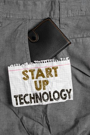 Writing note showing Start Up Technology. Business concept for Young Technical Company initially Funded or Financed Small wallet inside trouser front pocket near notation paper