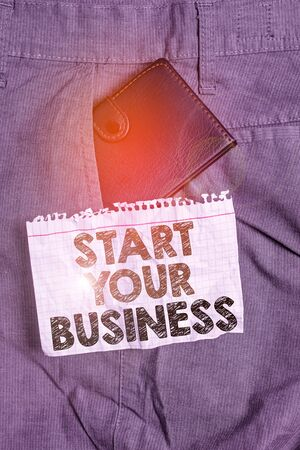 Writing note showing Start Your Business. Business concept for going into a New Venture Create New Product Services Small wallet inside trouser front pocket near notation paper