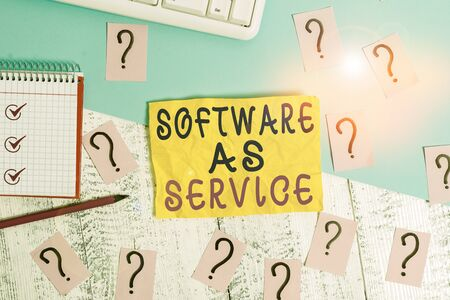 Writing note showing Software As Service. Business concept for On Deanalysisd licensed on Subscription and centrally hosted Writing tools and scribbled paper on top of the wooden table Stock Photo