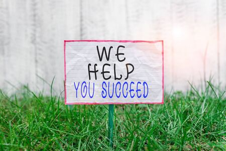 Text sign showing We Help You Succeed. Business photo text Aided Supported Funded someone to reach his dreams Crumpled paper attached to a stick and placed in the green grassy land