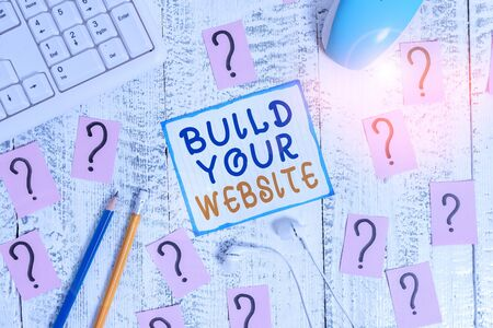 Writing note showing Build Your Website. Business concept for Setting up an ecommerce system to market a business Writing tools and scribbled paper on top of the wooden table