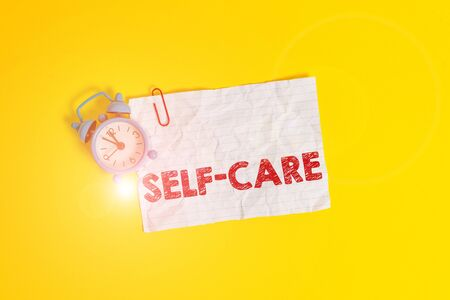 Text sign showing Self Care. Business photo showcasing the practice of taking action to improve one s is own health Metal alarm clock clip blank crushed note sheet colored background