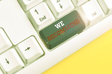 Word writing text We Recommend. Business photo showcasing suggest that someone or something would be good or suitable White pc keyboard with empty note paper above white background key copy space