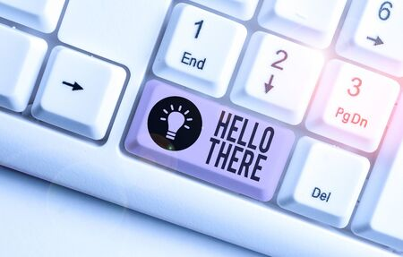 Writing note showing Hello There. Business concept for a way to get someone s is attention more strongly upon greeting White pc keyboard with note paper above the white background