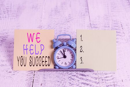 Writing note showing We Help You Succeed. Business concept for Aided Supported Funded someone to reach his dreams Mini blue alarm clock standing above buffer wire between two paper Stock Photo