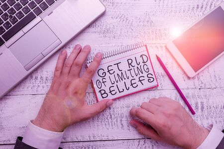 Writing note showing Get Rid Of Limiting Beliefs. Business concept for remove negative beliefs and think positively Hand hold note paper near writing equipment and smartphone