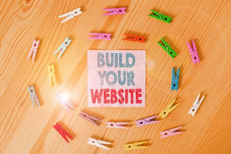 Conceptual hand writing showing Build Your Website. Concept meaning Setting up an ecommerce system to market a business Colored crumpled papers wooden floor background clothespin Stock Photo