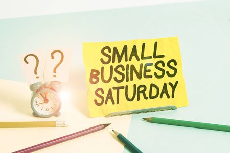 Text sign showing Small Business Saturday. Business photo text American shopping holiday held during the Saturday Mini size alarm clock beside stationary placed tilted on pastel backdrop