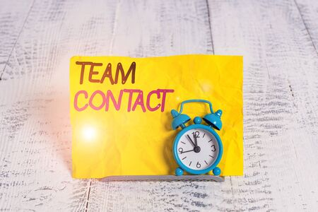 Word writing text Team Contact. Business photo showcasing The interaction of the individuals on a team or group Mini blue alarm clock stand tilted above buffer wire in front of notepaper