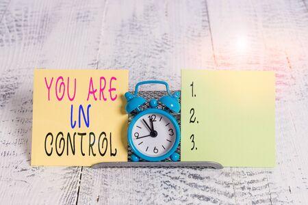 Schreiben Sie eine Notiz, die zeigt, dass Sie die Kontrolle haben. Geschäftskonzept für die Verantwortung über eine Situation Verwaltungsbehörde Mini blauer Wecker stehend über Pufferdraht zwischen zwei Papieren