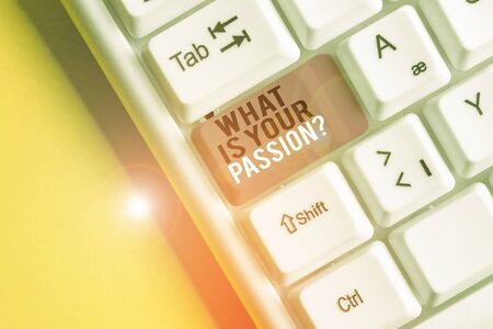 Text sign showing What Is Your Passion Question. Business photo text asking about his strong and barely controllable emotion White pc keyboard with empty note paper above white background key copy space