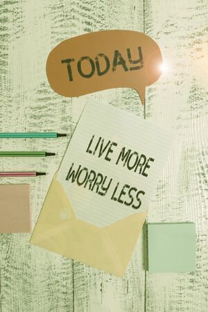 Writing note showing Live More Worry Less. Business concept for Have a good attitude motivation be careless enjoy life Envelop speech bubble paper sheet ballpoints notepads wooden background Stock fotó