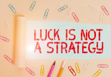 Writing note showing Luck Is Not A Strategy. Business concept for it is not being Lucky when planned intentionally Stationary and torn cardboard placed above plain pastel table backdrop