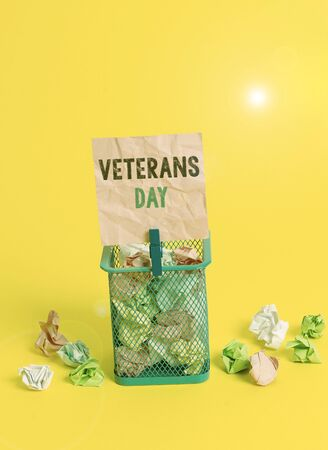 Handwriting text writing Veterans Day. Conceptual photo a public holiday to honour US veterans and victims of all wars Trash bin crumpled paper clothespin empty reminder office supplies yellow