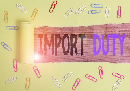 Text sign showing Import Duty. Business photo text tax imposed by a government on goods from other countries Paper clip and torn cardboard placed above a wooden classic table backdrop