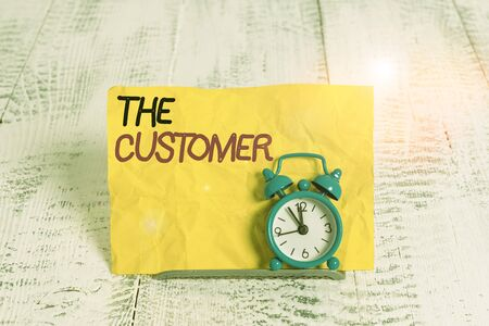 Word writing text The Customer. Business photo showcasing demonstrating or organization that buys goods or services from a store Mini blue alarm clock stand tilted above buffer wire in front of notepaper Stockfoto