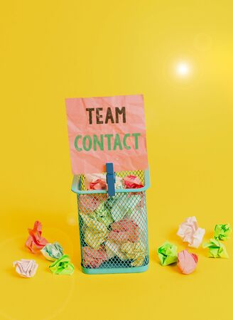 Handwriting text writing Team Contact. Conceptual photo The interaction of the individuals on a team or group Trash bin crumpled paper clothespin empty reminder office supplies yellow