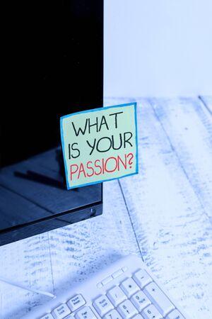 Escritura de texto ¿Cuál es tu pregunta de pasión? Fotografía conceptual preguntando por su emoción fuerte y apenas controlable Papel de notación pegado a la pantalla del monitor de la computadora negra cerca del teclado blanco Foto de archivo