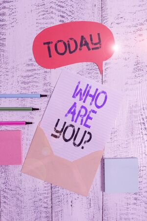 Writing note showing Who Are You Question. Business concept for Identify yourself description demonstratingal characteristics Envelop speech bubble paper sheet ballpoints notepads wooden background
