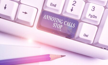 Conceptual hand writing showing Annoying Calls Stop. Concept meaning Prevent spam phones Blacklisting numbers Angry caller White pc keyboard with note paper above the white background