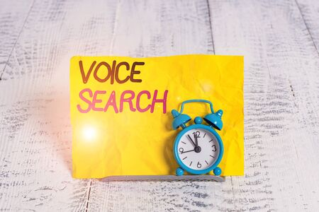 Word writing text Voice Search. Business photo showcasing allows the user to use a voice comanalysisd to search the Internet Mini blue alarm clock stand tilted above buffer wire in front of notepaper