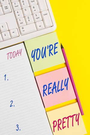 Text sign showing You Re Really Pretty. Business photo text She looks very charming Attractive in Delicate way Empty papers with copy space on the yellow background table