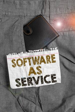 Writing note showing Software As Service. Business concept for On Deanalysisd licensed on Subscription and centrally hosted Small wallet inside trouser front pocket near notation paper