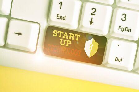 Text sign showing Start Up Technology. Business photo showcasing Young Technical Company initially Funded or Financed White pc keyboard with empty note paper above white background key copy space