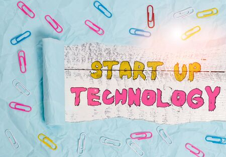 Writing note showing Start Up Technology. Business concept for Young Technical Company initially Funded or Financed Paper clip and torn cardboard on wood classic table backdrop 스톡 콘텐츠