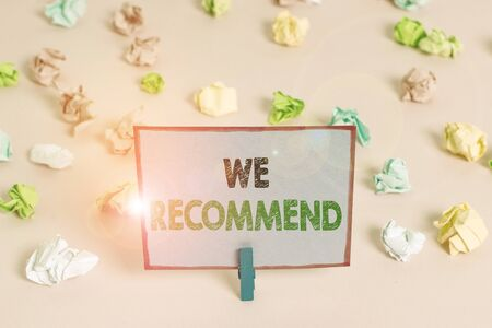 Writing note showing We Recommend. Business concept for suggest that someone or something would be good or suitable Colored crumpled papers empty reminder pink floor background clothespin