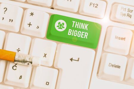 Handwriting text writing Think Bigger. Conceptual photo being able to dream and visualise what you can achieve White pc keyboard with empty note paper above white background key copy space