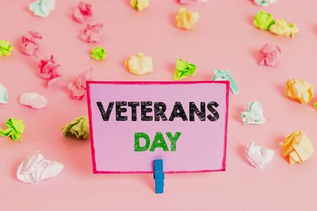 Writing note showing Veterans Day. Business concept for a public holiday to honour US veterans and victims of all wars Colored crumpled papers empty reminder pink floor background clothespin